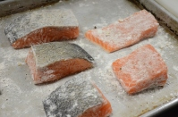 Dusting the seasoned salmon fillets with flour.