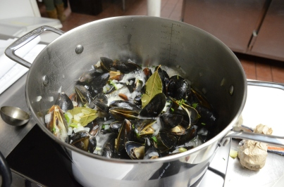 Steaming the mussels in a fragrant broth of bay leaves, thyme, and white wine.